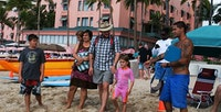 Family on Waikiki Beach receives tips from Beach Boy