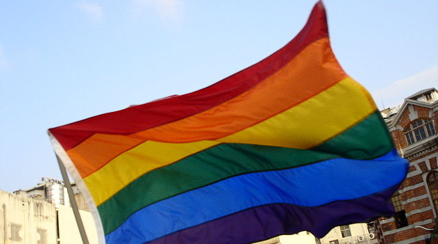 Rainbow flag flying with blue skies in back