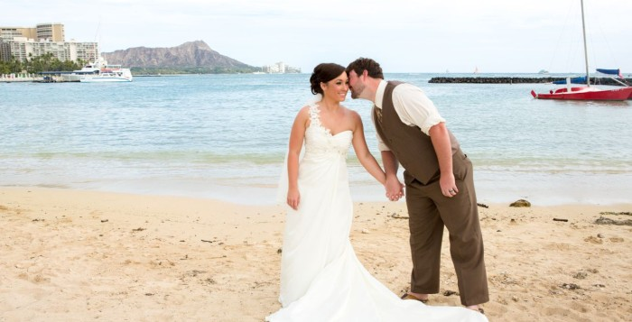 Husband kissing bride on Waikiki beach