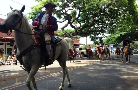 A man in costume rides a horse through the Koloa Town Parade