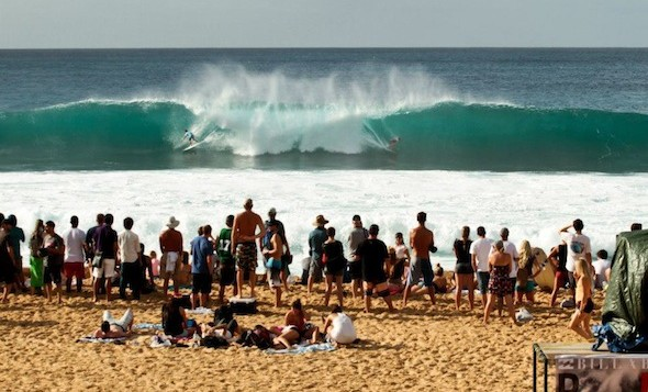 Spectators watch as surfers catch a huge wave barreling at Pipeline on Oahu's north shore