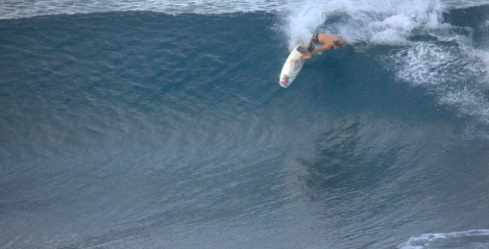 A surfer rides the top of a giant wave in Hawaii