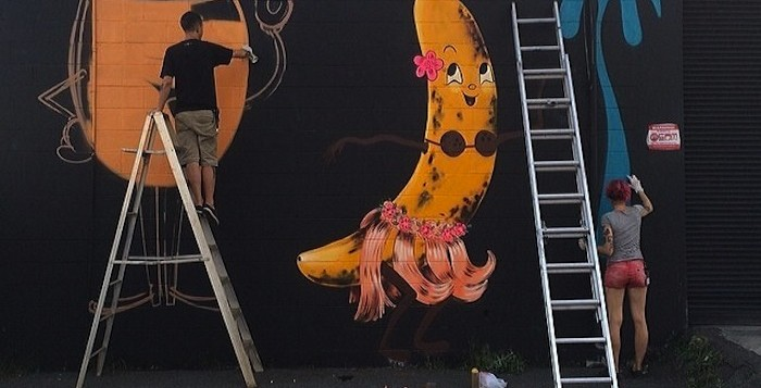 Two artists work on a mural in Kakaako of a banana wearing a hula skirt