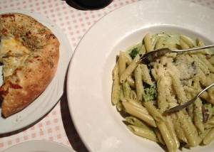 A plate of cheesy focaccia bread and bowl of creamy pesto pasta