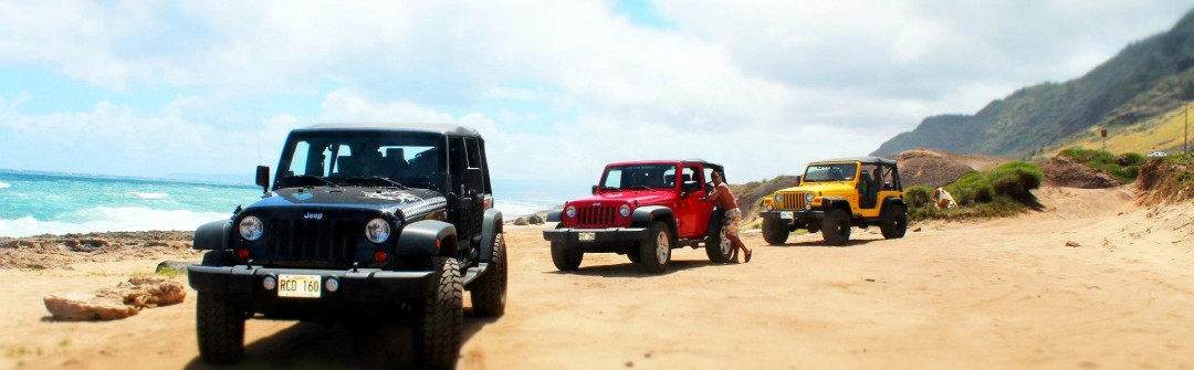 3 Jeeps sitting on a dirt road