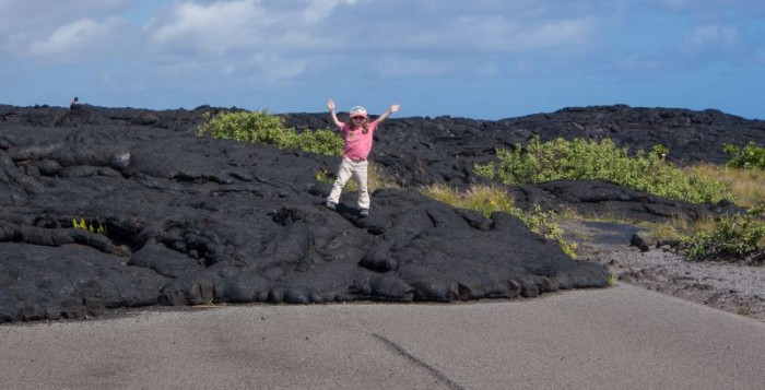 A girl holds up her arms bechause she is happy about hawaii