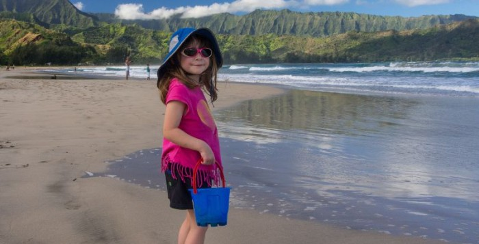 A small girls stands on a beach in Kauai