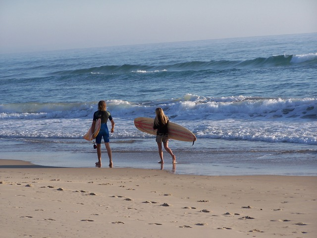 Boy and girl waling on the beach in Hawaii carrying  surfboards