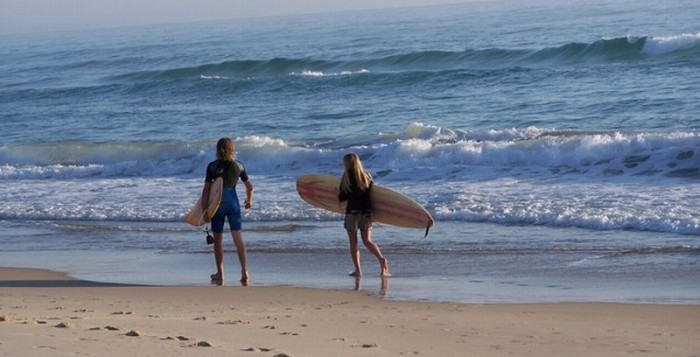 People with surfboards on the beach