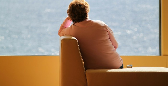 woman on sofa looking out at the ocean