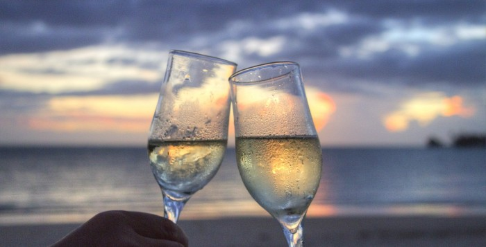 2 glasses of wine held up on a sunset