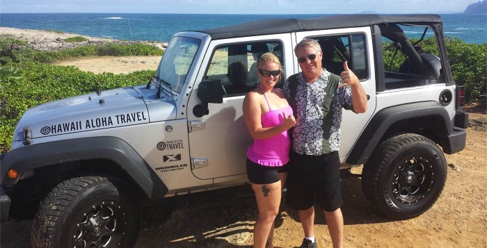 A happy couple poses in front of Hawaii Jeep Tours jeep