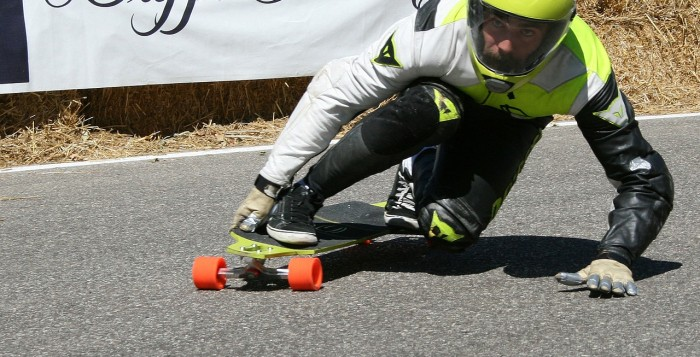 A skateboarder races downlhill