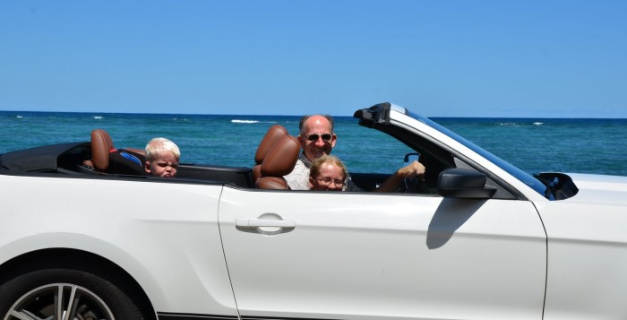 Family driving in Hawaii in Mustang convertible