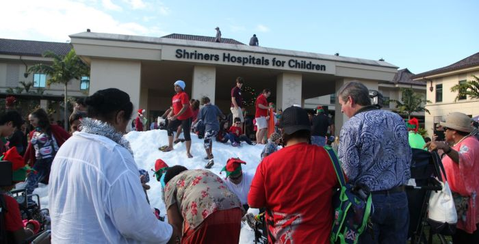people playing in snow in front of Shriners hospital in Hawaii on Oahu
