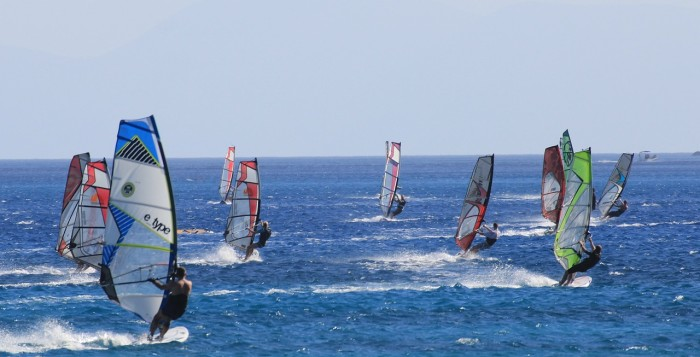 A group of windsurfers on the water
