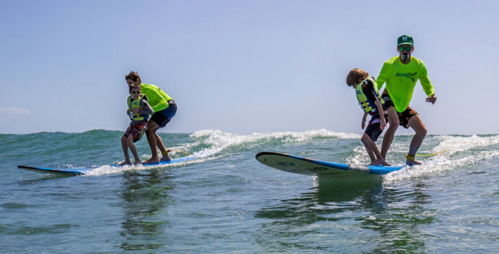 A photo of kids with disabilities surfing.