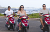 Three people driving mopeds