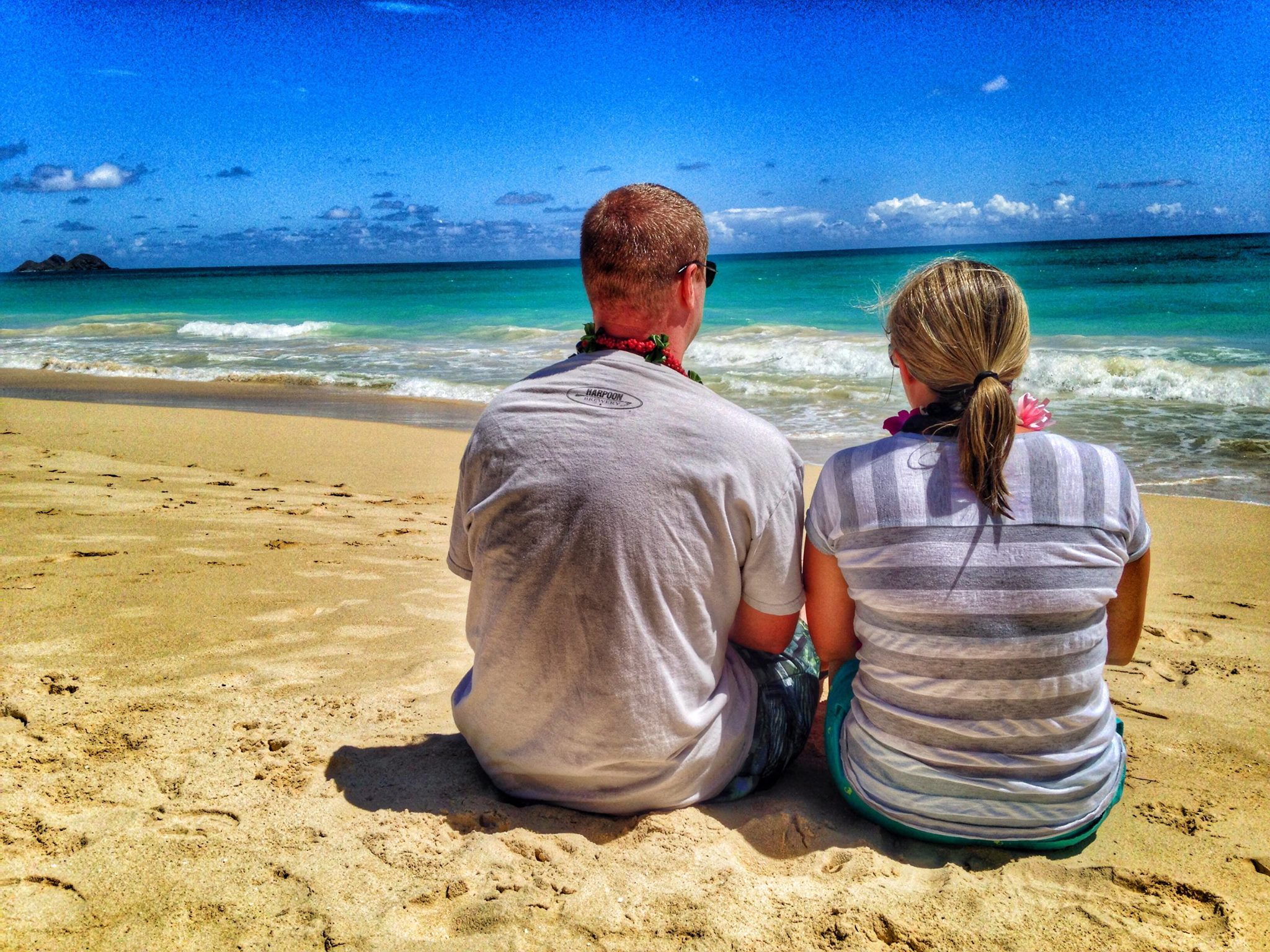 couple on a Hawaii beach looking out at the ocean