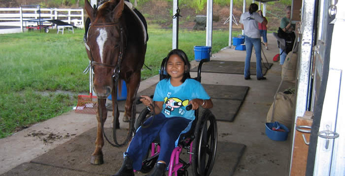 A girl in a wheelchair next to a horse