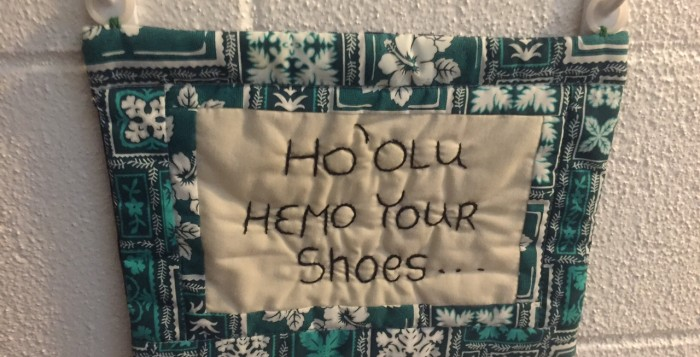 sign asking guests to remove their shoes in hawaiian