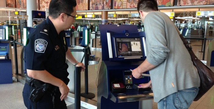 a man using a passport kiosk and an officer looking on