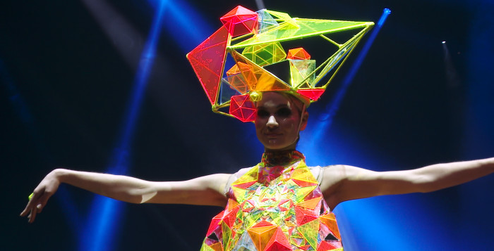 a woman in a fashion show with a multi-colored headdress