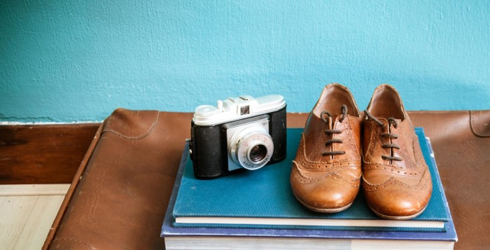 a suitcase with shoes and a camera
