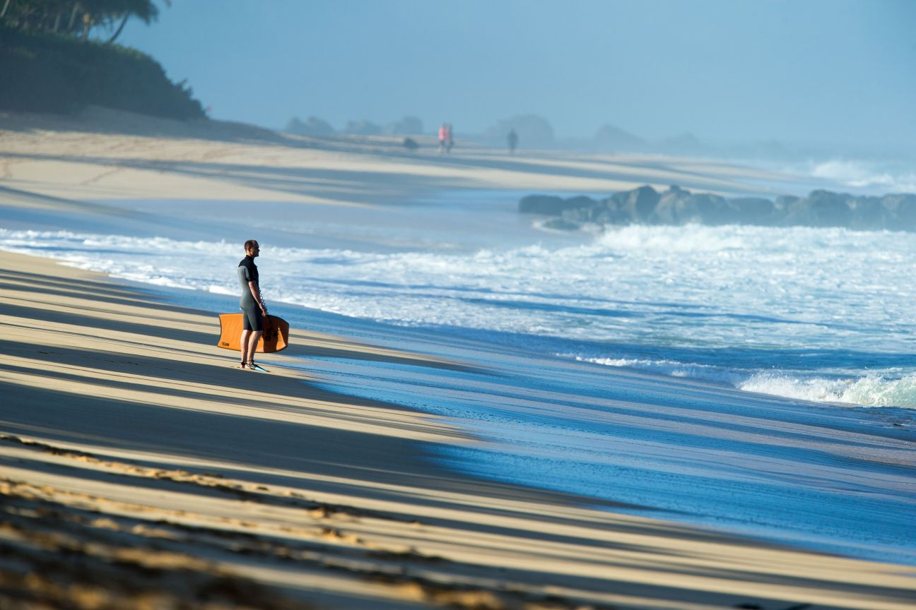 Man holding surfboard on North Shore of Oahu