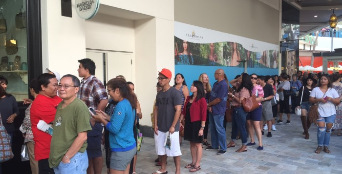 a line of customers waiting to get into the magnolia bakery