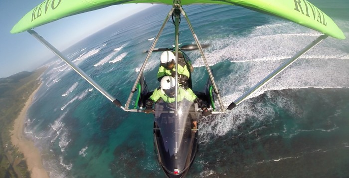 two people in a powered hang glider above the ocean