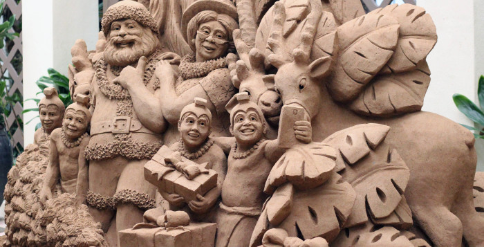a sand sculpture of santa claus taking a selfie