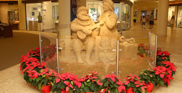 a sand sculpture of santa claus serenading mrs. claus with an ukulele