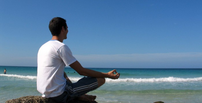 a man meditating by the ocean