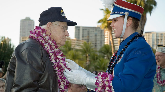 a parade participant putting a lei around a military veteran