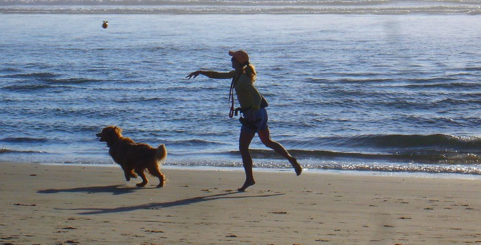 a woman throwing a ball to a dog at the beach