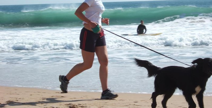 a woman jogging with her dog on the beach