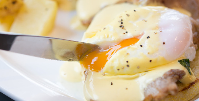 a knife cutting into eggs benedict