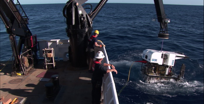 men on a boat reeling in a ROV