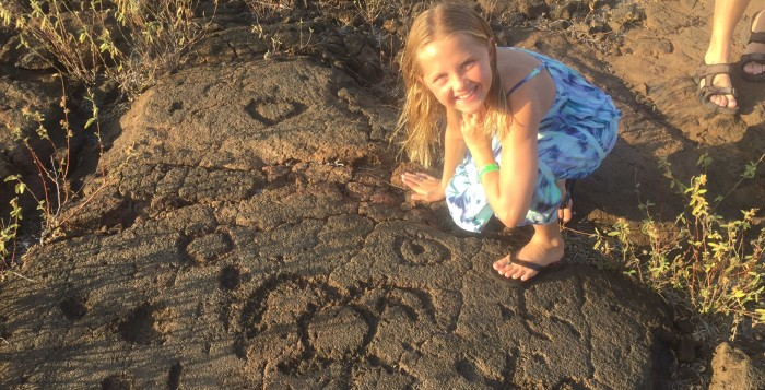 a young girl squatting next to petroglyphs