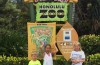 three children standing in front of the honolulu zoo sign