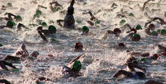 people swimming in the ocean during a triathalon