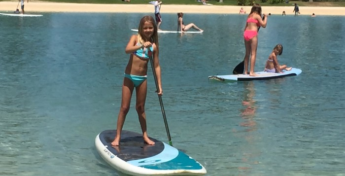 a young girl stand-up paddleboarding