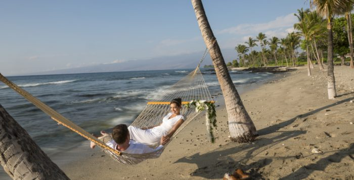 two people in a hammock on the beach