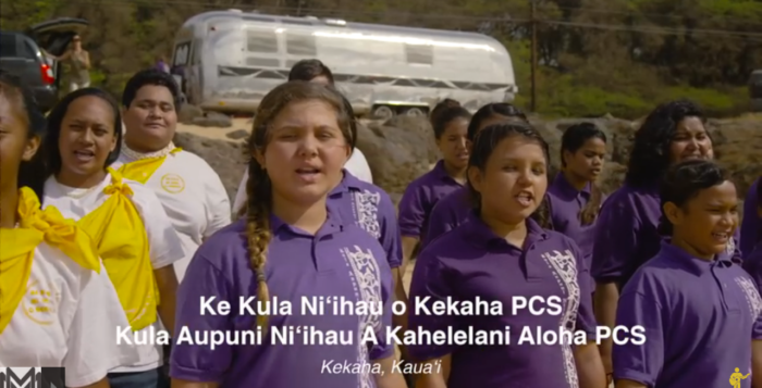 children singing with purple shirts on