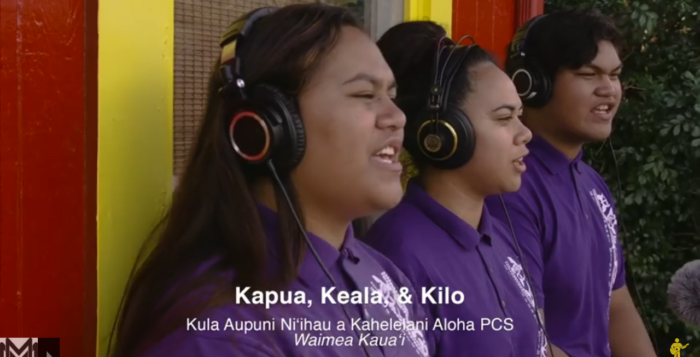three girls singing with purple shirts on
