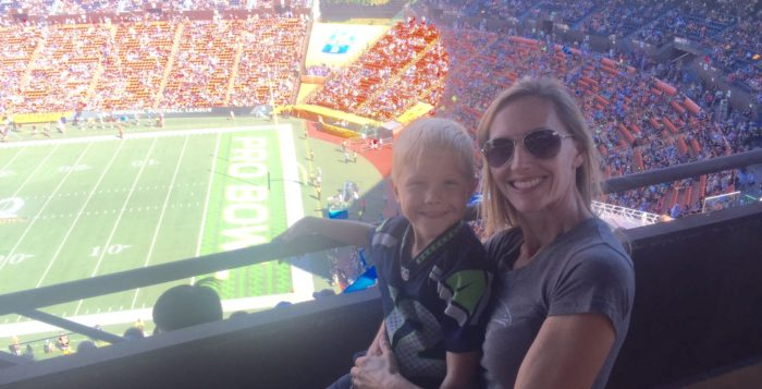 a woman and a small boy at a football game
