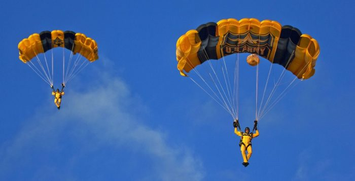 two people skydiving with opened parachutes