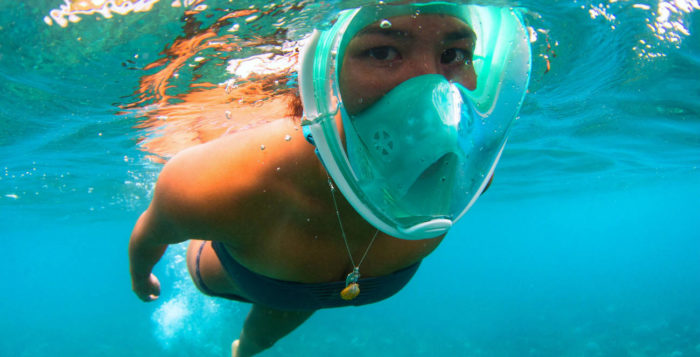 a man swimming with a snorkel mask on