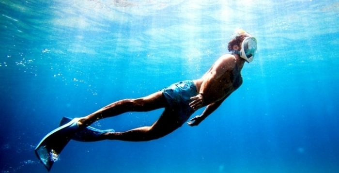 a man swimming to the surface of the water with a snorkel mask on